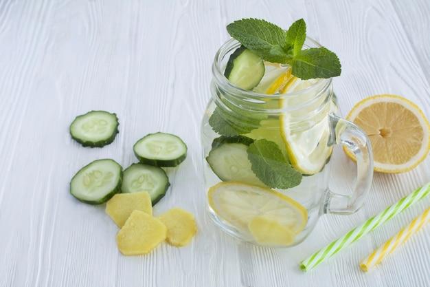 白い木製の背景のガラスにレモン、キュウリ、生姜を入れた生意気な水痩身または注入水。閉じる。