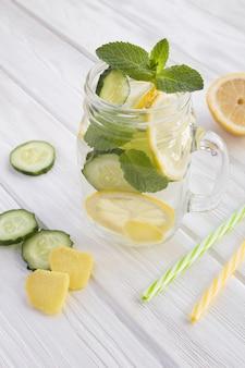 白い木製の背景のガラスにレモン、キュウリ、生姜を入れた生意気な水痩身または注入水。場所は垂直です。