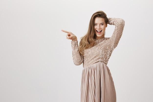 Sassy donna in abito elegante che punta a sinistra