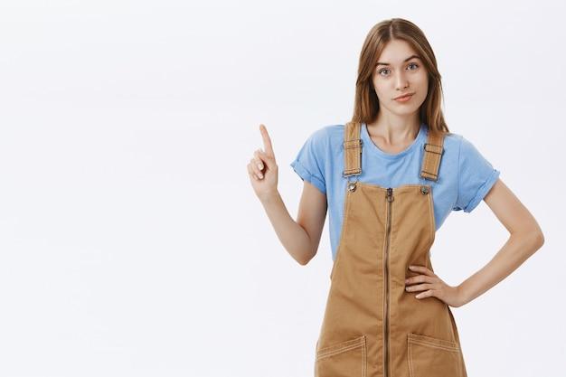 Нахальная молодая девушка колледжа трясет пальцем или указывает вверх