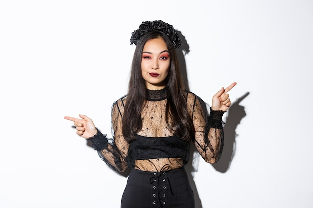 Sassy young evil witch with gothic makeup and wreath, looking arrogant while pointing fingers sideways, showing two halloween themed banners, standing over white background.