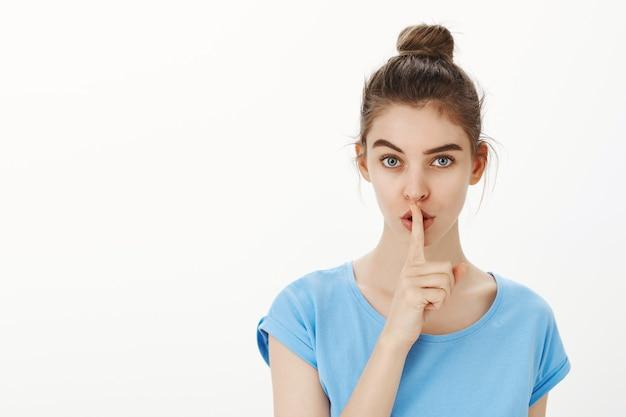 生意気な若い女性はあなたにシーッ、唇に指を押して身をかがめる