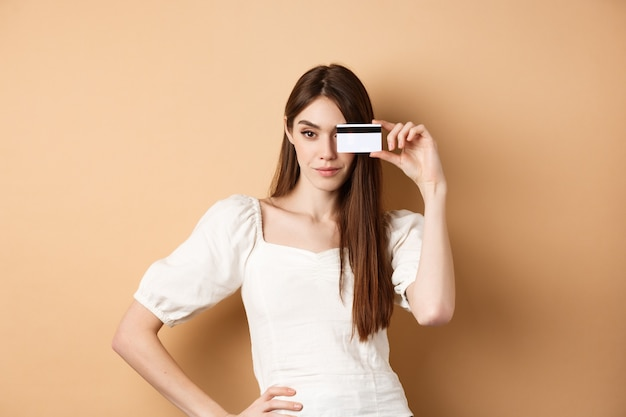 Sassy young woman showing plastic credit card on face and looking determined going on shopping stand...
