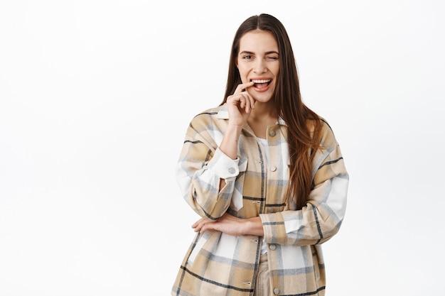 生意気な若い女性がウインクしてあなたに微笑んで、確かに、店に行くか、移動することを奨励し、自信を高め、何かをほのめかし、白い壁の上に立ってください