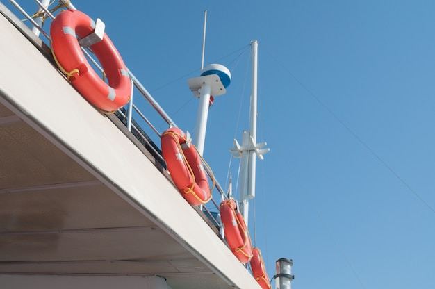Satellite antenna and lifebuoy rings on the ship deck