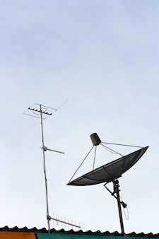 Satellite dish and Radio Antenna on the house Roof Vertical