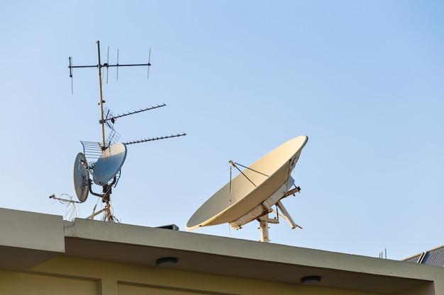 Спутниковая тарелка и телевизионные антенны на крыше дома с фоном голубого неба.