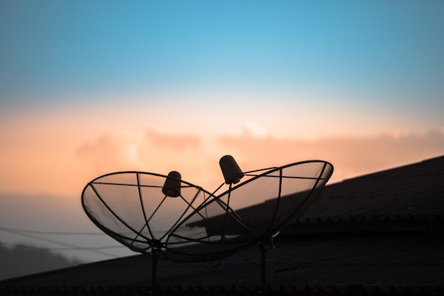Satellite dish or antenna dish on the house roof with beautiful blue sky in the morning.