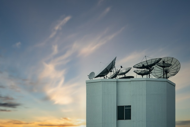Satellite dish antenna on top of the building with beautiful sky