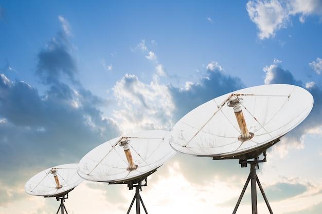 Satellite dish antennas under sky.