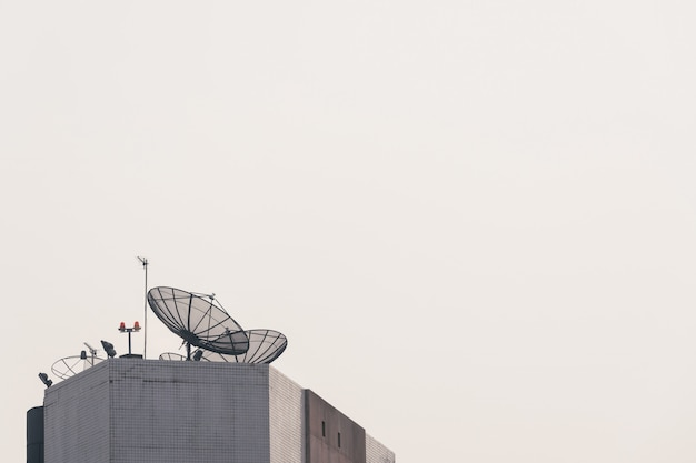 Satellite dish on high-rise building with clear sunset sky in background