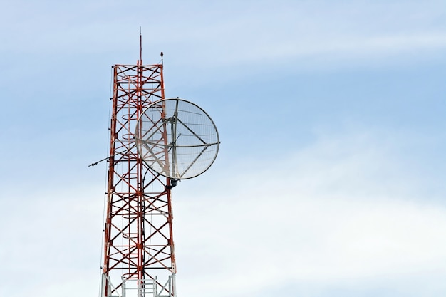 Satellite dish on telecommunication radio antenna tower with blue sky