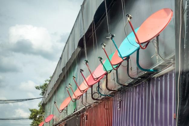 Спутниковые тарелки антенны многоцветные прикрепленные сортированные стены