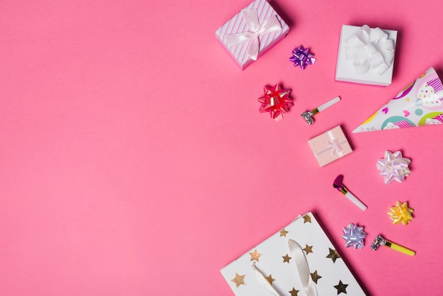 Satin bow; gift boxes; party hat and paper bag on pink background