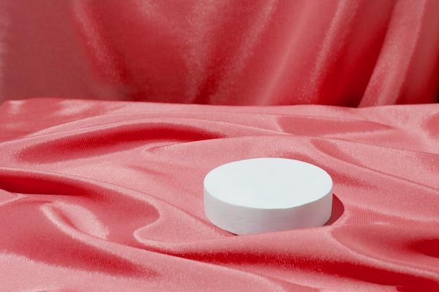 化粧品や香水用のサテン生地の折り目と表彰台または台座