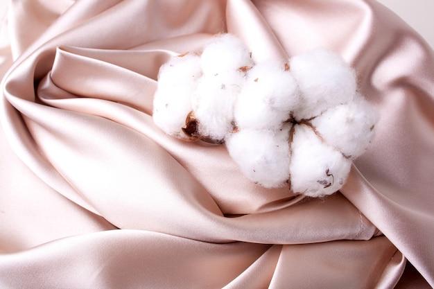 サテンピーチ生地と綿の背景