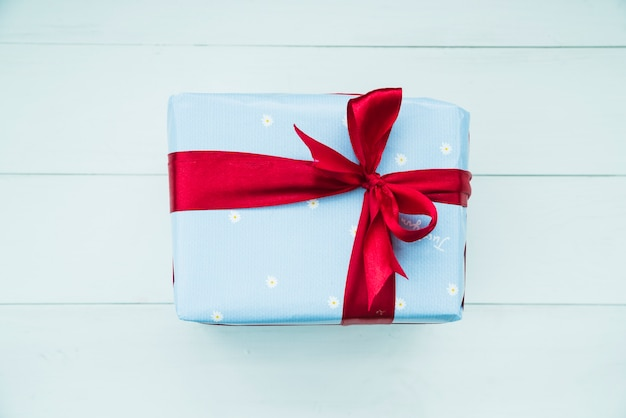 Satin red ribbon over the blue gift box on wooden background