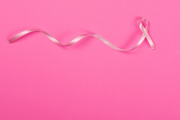 Satin ribbon sign on the pink background and breast cancer concept