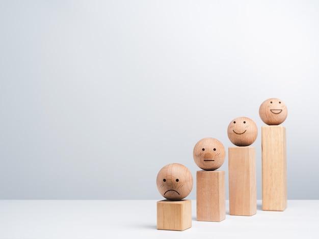 Удовлетворение и процесс роста бизнеса и концепция экономического улучшения. смайлик, эмоции сталкиваются с деревянными шарами и деревянными кубическими блоками, диаграмма шагов на белом фоне с копией пространства, минимальный стиль.