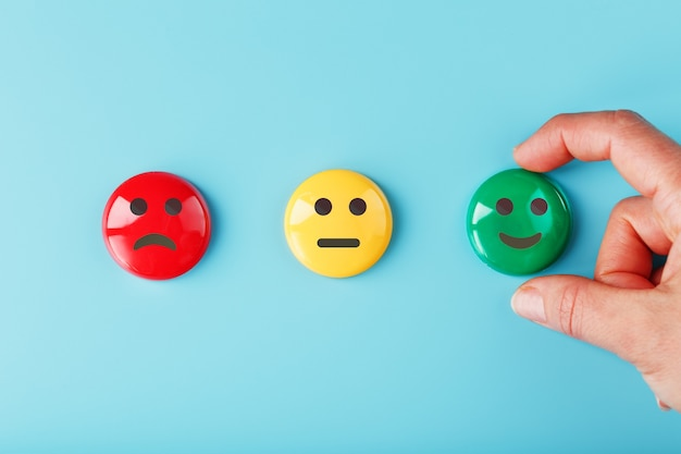 Satisfaction emotion icons red displeased, yellow neutral and green smiling emoticon on a blue surface with a hand
