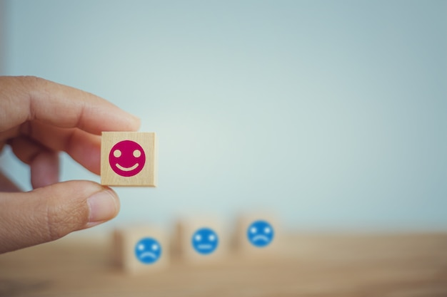 Satisfaction survey concept: hand chooses a smiley face on wood block cube. depicts the best excellent business services rating customer experience.
