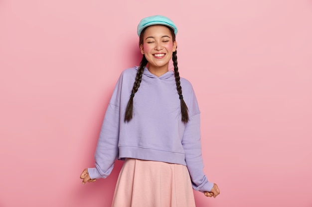Satisfied adorable young korean female model with rouge cheeks, laughs from joy, wears blue cap, oversized jumper and skirt