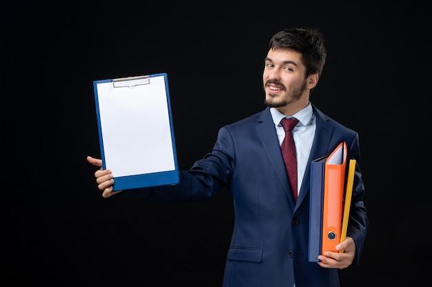 いくつかの文書を保持し、孤立した暗い壁にそれらの1つを示すスーツで満足している大人