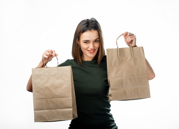 Satisfied adult woman carrying paper bags after shopping on white