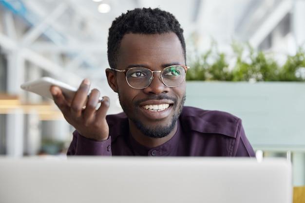 Довольный африканец-мужчина в приемной отправляет информацию клиентам через смартфон, пользуется высокоскоростным интернетом.