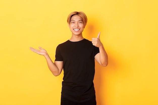 Довольный и счастливый привлекательный корейский парень улыбается, показывает вверх большие пальцы в одобрении от радости, держит что-то под рукой, стоит на желтой стене