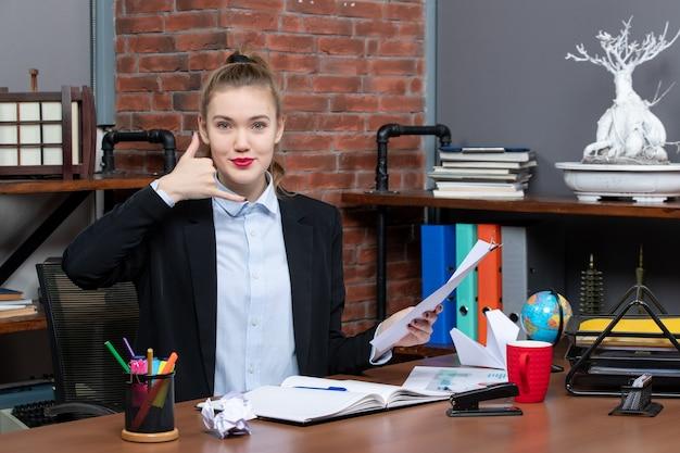 テーブルに座って、オフィスで私をジェスチャーと呼んで文書を持っている満足して前向きな若い女性
