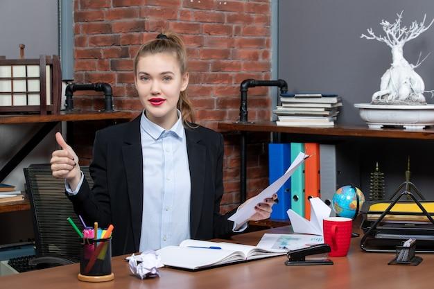 Довольная и позитивная молодая дама сидит за столом и держит документ, делая жест в офисе