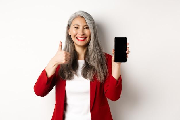 Donna d'affari anziana asiatica soddisfatta che mostra lo schermo vuoto dello smartphone e il pollice in su, lodando la promozione online o l'app aziendale, in piedi su sfondo bianco