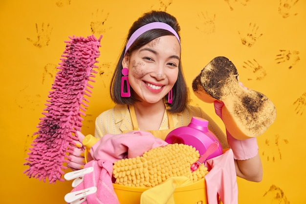 Satisfied asian housewife wears headband and earrings has dirty face after removing dust poses with mop sponge cleans everything in house isolated over yellow wall