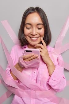 Удовлетворенная азиатская миллениальная девушка использует информацию о поиске по мобильному телефону в интернете, делает заказ по сотовому поиску работа в отпуске улыбается счастливо, носит повседневную рубашку, приклеенную к серой стене