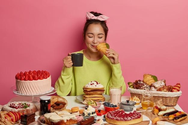 La donna asiatica soddisfatta mangia deliziosi croissant per ogni pasto della giornata, beve il tè, pone al tavolo festivo, essendo dipendente da cibi dolci, pone su sfondo rosa.