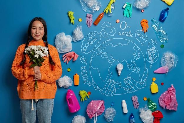 두 개의 땋은 머리를 가진 만족스러운 아시아 여성은 주황색 점퍼를 입고 꽃다발을 들고 자연을 돌보고 생태 친화적이며 컴파일 된 쓰레기를 재활용 할 준비가되었습니다.