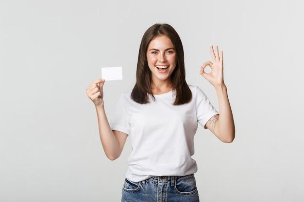 Удовлетворенная привлекательная девушка брюнет показывает кредитную карту и хорошо жест, рекомендует банк.
