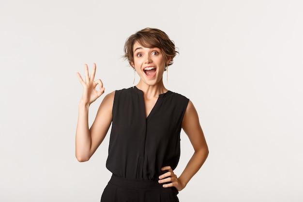 Удовлетворенная привлекательная молодая женщина показывает нормальный жест в знак одобрения, рекомендует продукт, дает совет, стоя белым.