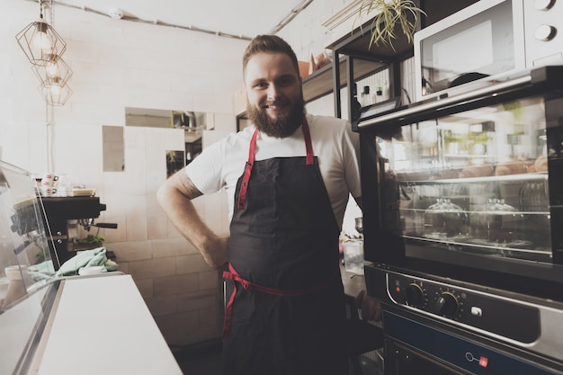 Satisfied bearded baker apron stands next to oven