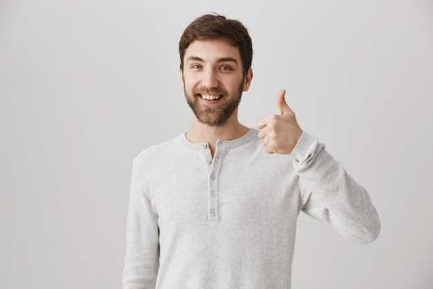 Satisfied bearded male customer show thumbs-up in approval