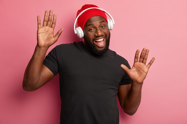 Satisfied bearded male youngster listens merry song in headphones, moves over pink background, boosts mood with cool music, feels upbeat, wears red hat and black t shirt.