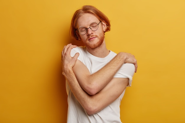 満足しているあごひげを生やした男はリラックスし、抱きしめ、肌寒い