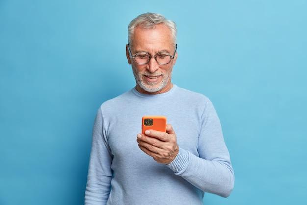 Довольный бородатый мужчина, сосредоточенный на смартфоне, серфит в интернете, отправляет текстовые сообщения в социальных сетях, использует современные технологии, носит повседневный синий джемпер, позирует в помещении