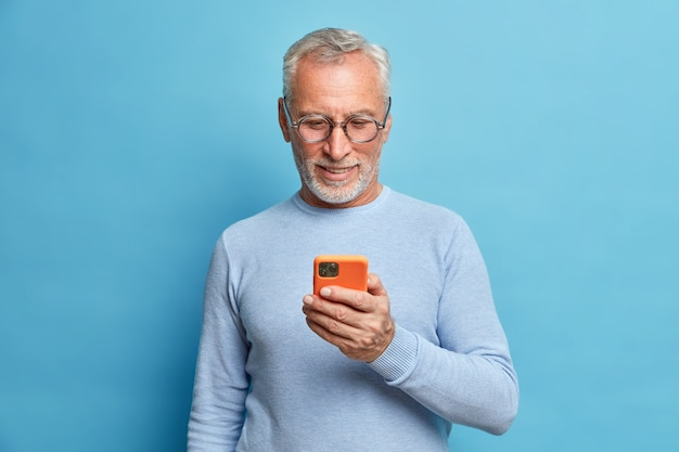 Satisfied bearded man focused in smart phone surfs internet sends text messages in social networks uses modern technologies wears casual blue jumper poses indoor