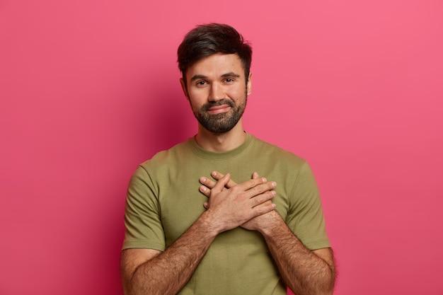 Satisfied bearded smiling man makes gratitude gesture