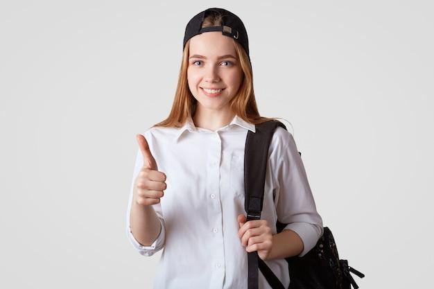 Довольная красивая школьница держит большой палец поднятым