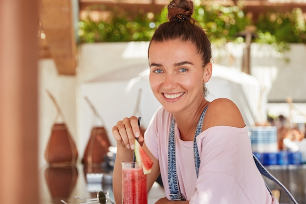 Satisfied beautiful woman with pleasant smile, drinks cocktail, sits at cafeteria, has hair bun and shining smile, being glad to spend vacations in tropical country.