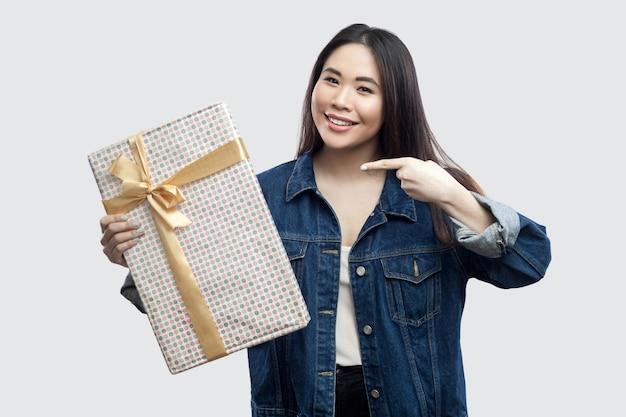 Удовлетворенная красивая молодая азиатская девушка в синей джинсовой куртке, стоящей и указывающей пальцем, чтобы представить с желтым бантом и зубастой улыбкой, глядя в камеру. крытый, изолированный, студийный снимок, серый фон