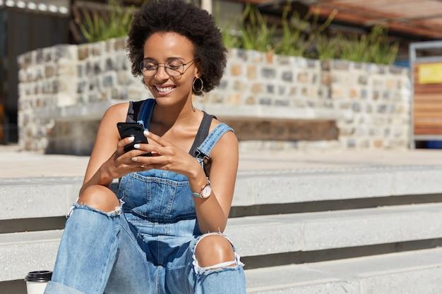 Blogger soddisfatto invia messaggi divertenti per post sul sito web personale, indossa una tuta sfilacciata, invia feedback, scarica file, indossa occhiali, posa sui gradini della città, copia spazio per il tuo testo pubblicitario